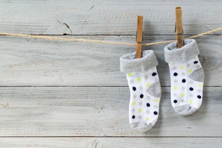 Baby socks hanging on clothesline on wooden background