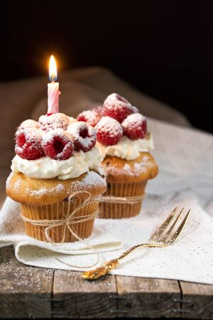 Muffins with soft cream and fresh raspberry powdered with sugar and decorated with burning candle, happy birthday card, rustic background