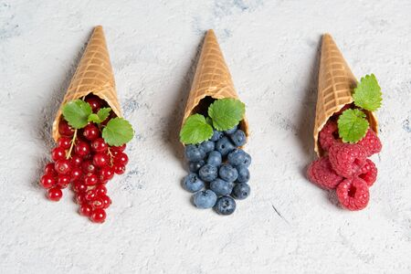 Fresh berries in waffle cones on stone background, raspberry, blueberry and redcurrant with mint leaves