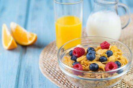 Healthy breakfast concept - cereals with berries, orange juice, orange slices and milk. Stock fotó