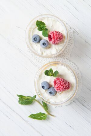 Two portions of homemade dessert cream with peaches, fresh berries and mint in a glass on a wooden table, top view Stock fotó