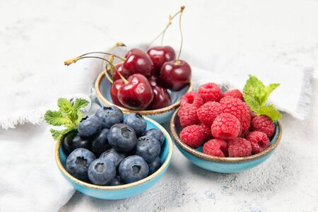 Assorted fresh juicy berries. Cherry, blueberry and raspberry in bowls