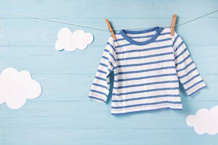 Vêtements de bébé garçon et nuages blancs mignons sur une corde à linge, fond bleu