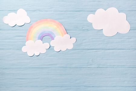 Children or baby background, white clouds with rainbow on the blue wooden background Stock Photo