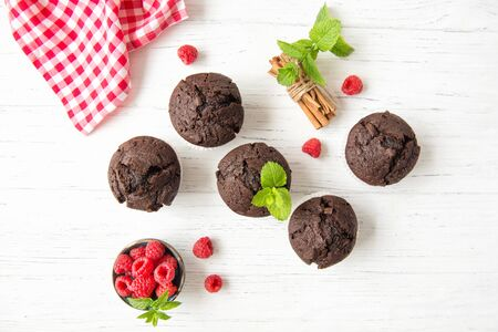 Chocolate muffins with raspberries and mint leaves on white wooden background, top view