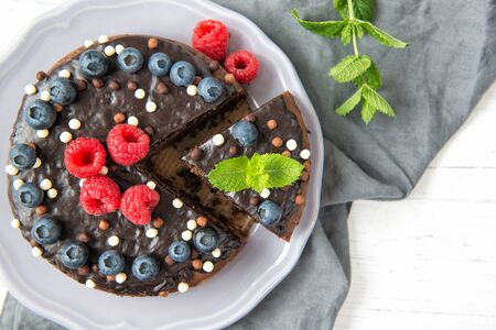 Chocolate cake with chocolate icing, raspberries, blueberries and mint leaves, top view