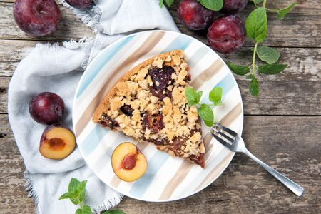 Piece of Plum Cake on a plate with ripe plums and mint leaves, wooden table