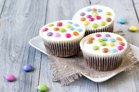 Cupcakes with white icing and colored smarties on the plate, wooden background