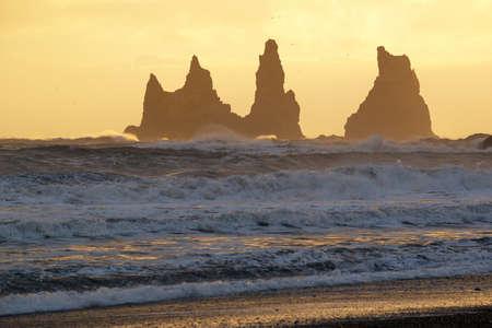 Golden sunset at Reynisdrangar cliffs on Black sand beach in Vik, Iceland