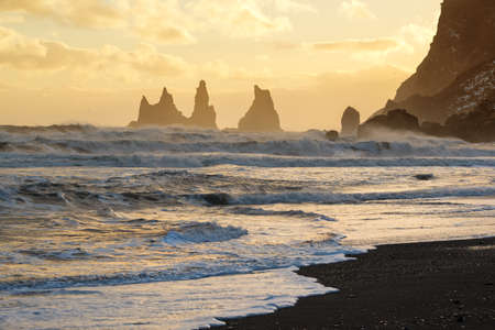 Sunset with golden sky behind the Reynisdrangar rocks, Vik black sand beach, Iceland