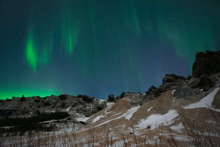 Aurora Borealis or Northern Lights above the mountains, Iceland Reklamní fotografie