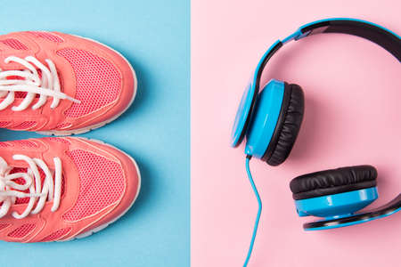 Bright pink sneakers and blue headphones on blue and pink background, top view Stock Photo