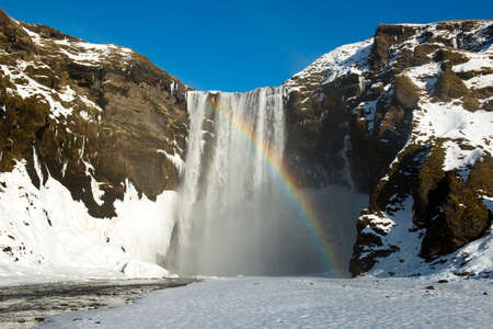 Winter landscape with Skogafoss waterfall and rainbow, Iceland Reklamní fotografie