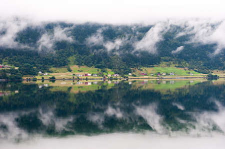 Rural landscape with houses, waterfall and clouds, mirror reflection in the water, Norway 免版税图像