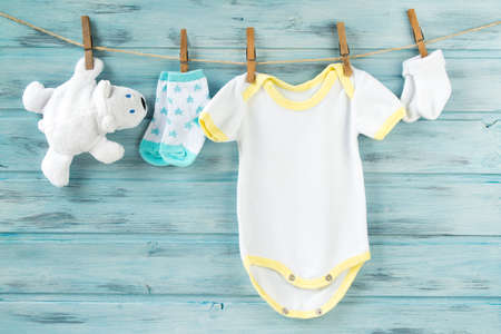Baby boy clothes, with socks and white bear toy on a clothesline