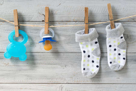 Teether, baby pacifier and socks hanging on clothesline on wooden background Reklamní fotografie
