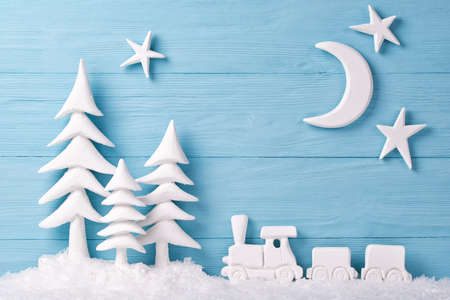 Christmas background with white christmas trees, toy train, snow, moon and stars, blue wooden background Stock Photo