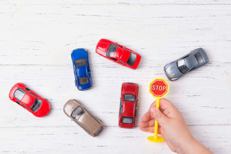 Child hands playing with miniature toy cars and stop sign, wooden background, top view