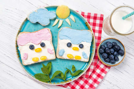 Cute penguin toasts with spread on a plate, food for kids ideas, top view