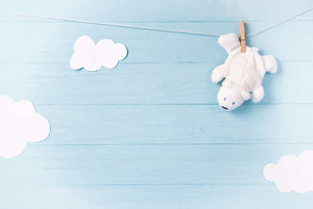 Baby boy background with white teddy bear toy on a clothesline and clouds Standard-Bild