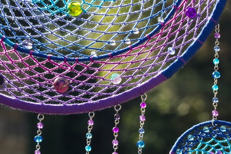 photo of a dreamcatcher made by hand, with using threads, beads and feathers rooster