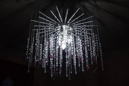 beautiful blurred silver chandelier glowing in the dark