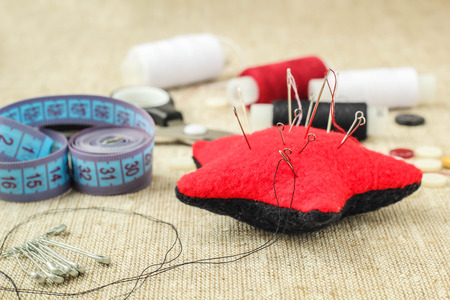 pin cushion with needles,thread and buttons for sewing