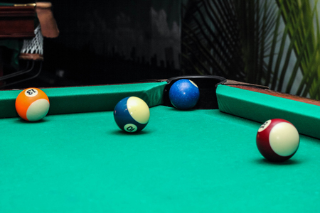 Billiard balls on green table and the blue ball in the pocket