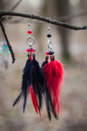 Red black and purple Dreamcatcher with bat made of feathers leather beads and ropes, hanging Stock Photo