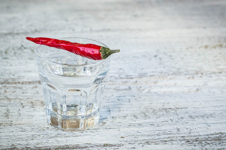 drunkard: Shot of vodka with cayenne pepper on an old white wooden table Stock Photo