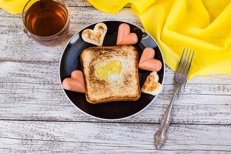 scrambled: breakfast for the celebration of Valentines day - toast with scrambled eggs in the form of hearts, sausages and tea