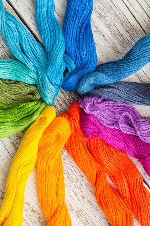 colorful sewing threads for embroidery on white wooden background