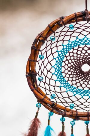 Blue and brown Dreamcatcher made of feathers leather beads and ropes, hanging