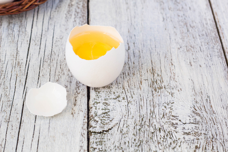 misfit: Broke One whole egg amongst white eggs in basket on a white wooden background Stock Photo