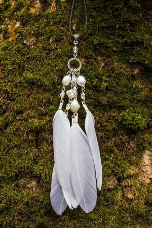 White pendant with feathers and beads in the forest, handmade.