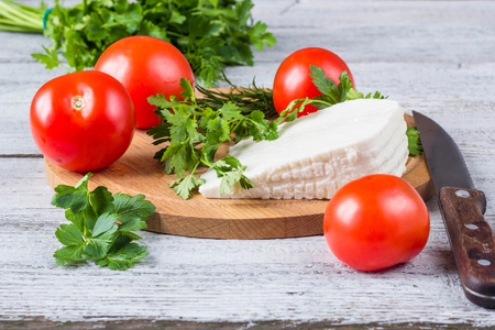 White brine cheese, knife, parsley, tomatoes on a wooden boards background