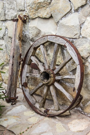 Old wooden and metall wheel on stone wall background Stock Photo