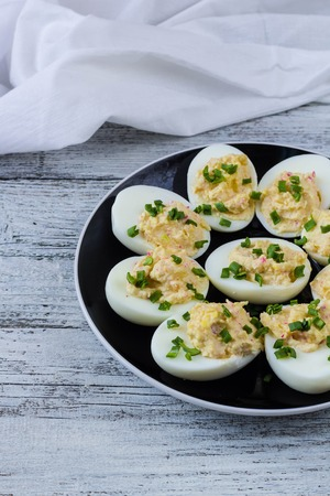 Home eggs stuffed with cheese and crab sticks topped with green onions