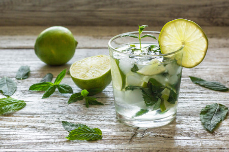 Mojito cocktail with lime and mint in highball glass on a white wooden background.