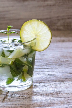 Mojito cocktail with lime and mint in highball glass on a white wooden background, toned