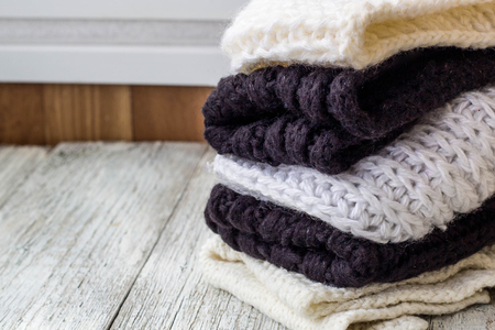 folded knitted things white and black on a white wooden background.
