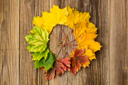 Colorful and bright background from a circle of autumn leaves, on a wooden background. Autumn concept.