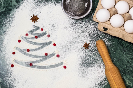 Ingredients for cooking christmas baking. Christmas tree with the flour, berries and anise star spices as a decoration and rolling pin, eggs, strainer
