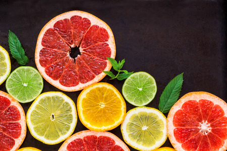 corner with oranges, lemons, limes, grapefruit and mint pattern on black. Flat lay, top view Stock Photo