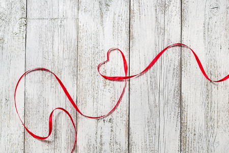Happy Valentines Day. Red Ribbon Heart on white wooden background.