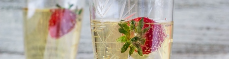 Banner of two champagne glasses and strawberries on white background