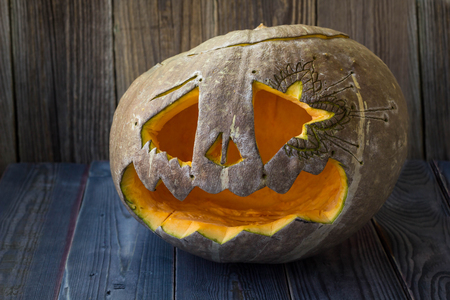 Jack o lanterns Halloween pumpkin face on wooden background. Stock Photo
