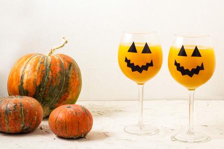 Autumn orange holiday pumpkin cocktail with halloween decor on the table.