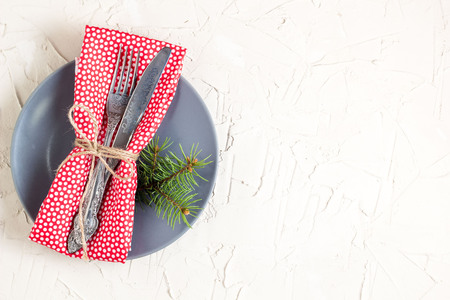 Christmas menu background with fork knife napkin and fir tree brunch on white table. Copy space, top view.
