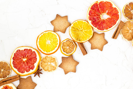 Border of Dried slices of various citrus fruits gingerbread and spices on white background with copyspace. Christmas frame